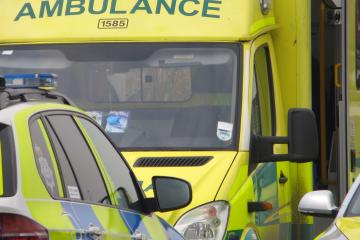 Ambulance and responder vehicles responding to medical emergency in urban street