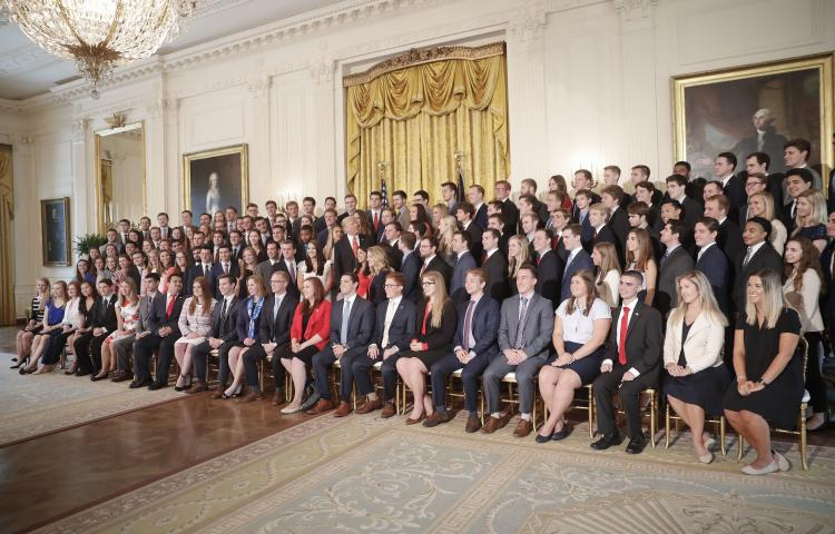 President Donald Trump, center, looks over his shoulder as he poses for a photo with outgoing White House interns in the East Room of the White House in Washington, Monday, July 24, 2017. (AP Photo/Pablo Martinez Monsivais)