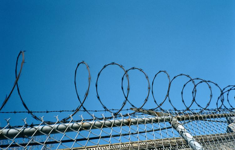 Jail fence with barbed wire on top.