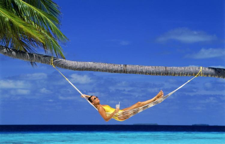 Woman relaxing in hammock under palm tree with tropical drink