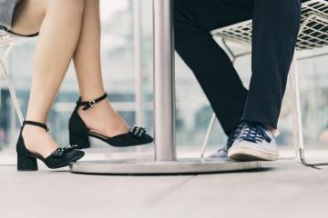 City businessman and woman meeting at sidewalk cafe, legs