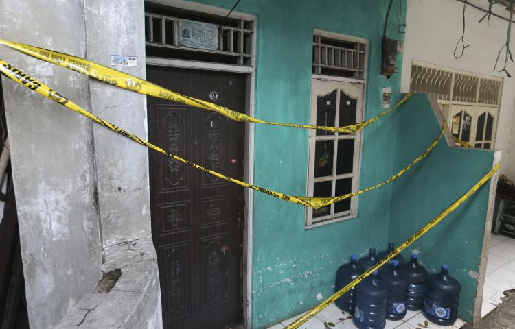 Police tape covers a home-based alcohol factory in Jakarta, Indonesia, Monday, April 9, 2018. Nearly 50 people have died in a little more than a week after drinking bootleg liquor in western Indonesia, including Jakarta, the capital, officials said Monday. (AP Photo/Achmad Ibrahim)