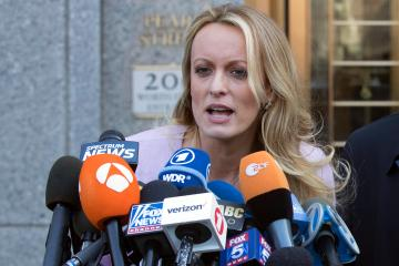 FILE - In this April 16, 2018, file photo, adult film actress Stormy Daniels speaks outside federal court in New York. A federal judge is set to hear arguments about whether to delay the case of Daniels, who claims she had an affair with President Donald Trump, after federal agents raided the president's personal lawyer's office and residence. U.S. District Judge James Otto will hold the hearing Friday, April 20, 2018, in Los Angeles. (AP Photo/Mary Altaffer, file)