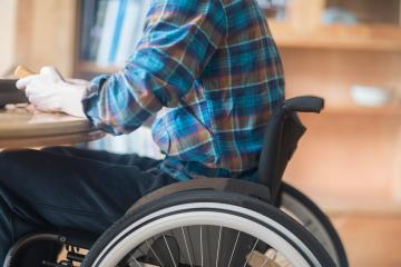 Young man using wheelchair connecting control panel and transformer at kitchen table