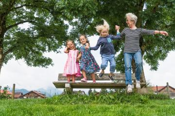 Grandmother and grandchildren in mid air jumping from park bench, Fuessen, Bavaria, Germany
