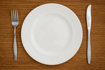 Studio shot of white plate with fork and knife