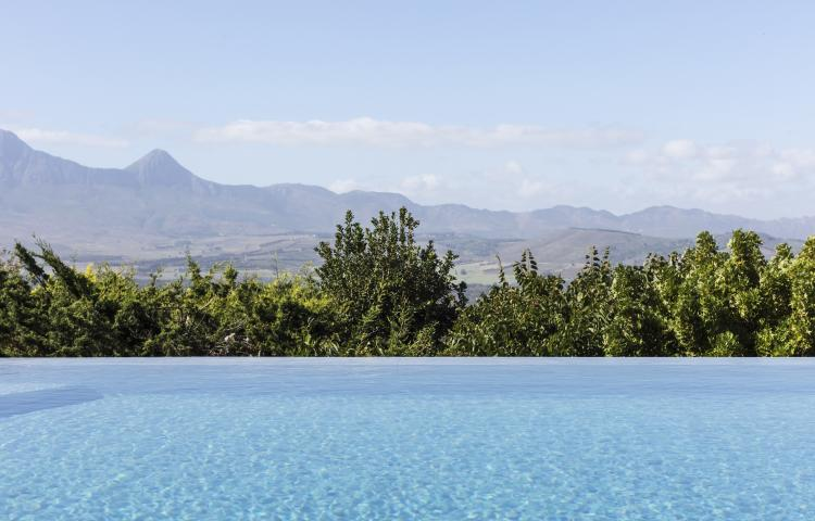 Tranquil luxury infinity pool with sunny mountain view